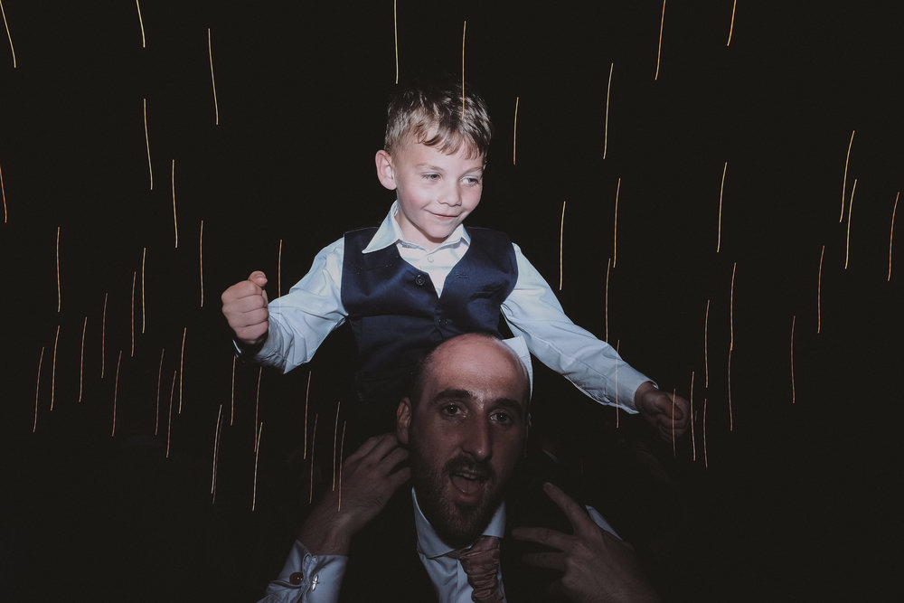 Child sitting on his father's head on dance floor