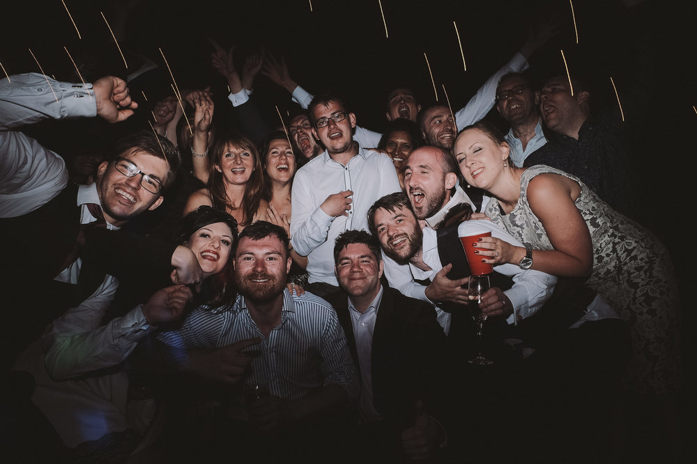 Wedding guests all pile in to photo on dance floor