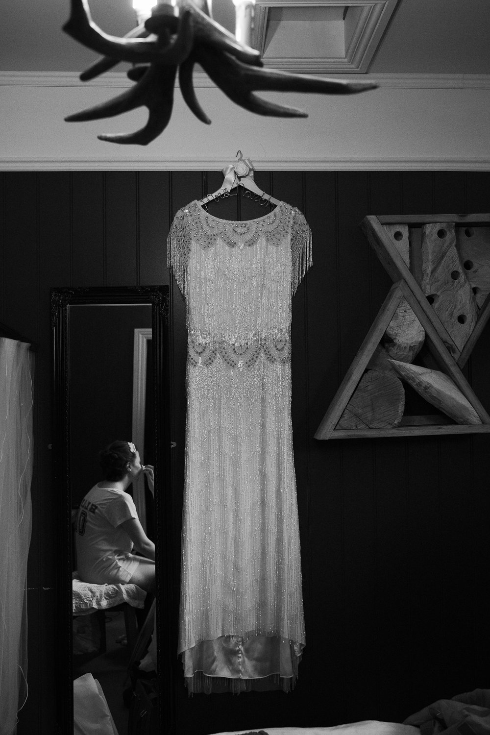 Balckand white photo of wedding dress hanging in hotel room