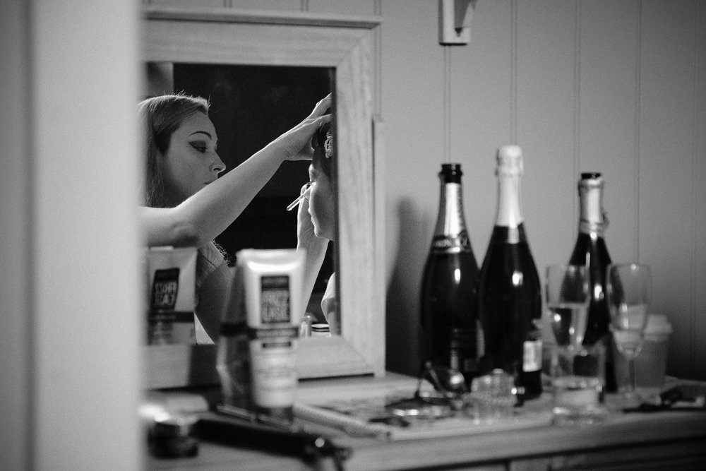 Black and white photo of bridal preparations reflected in a mirror