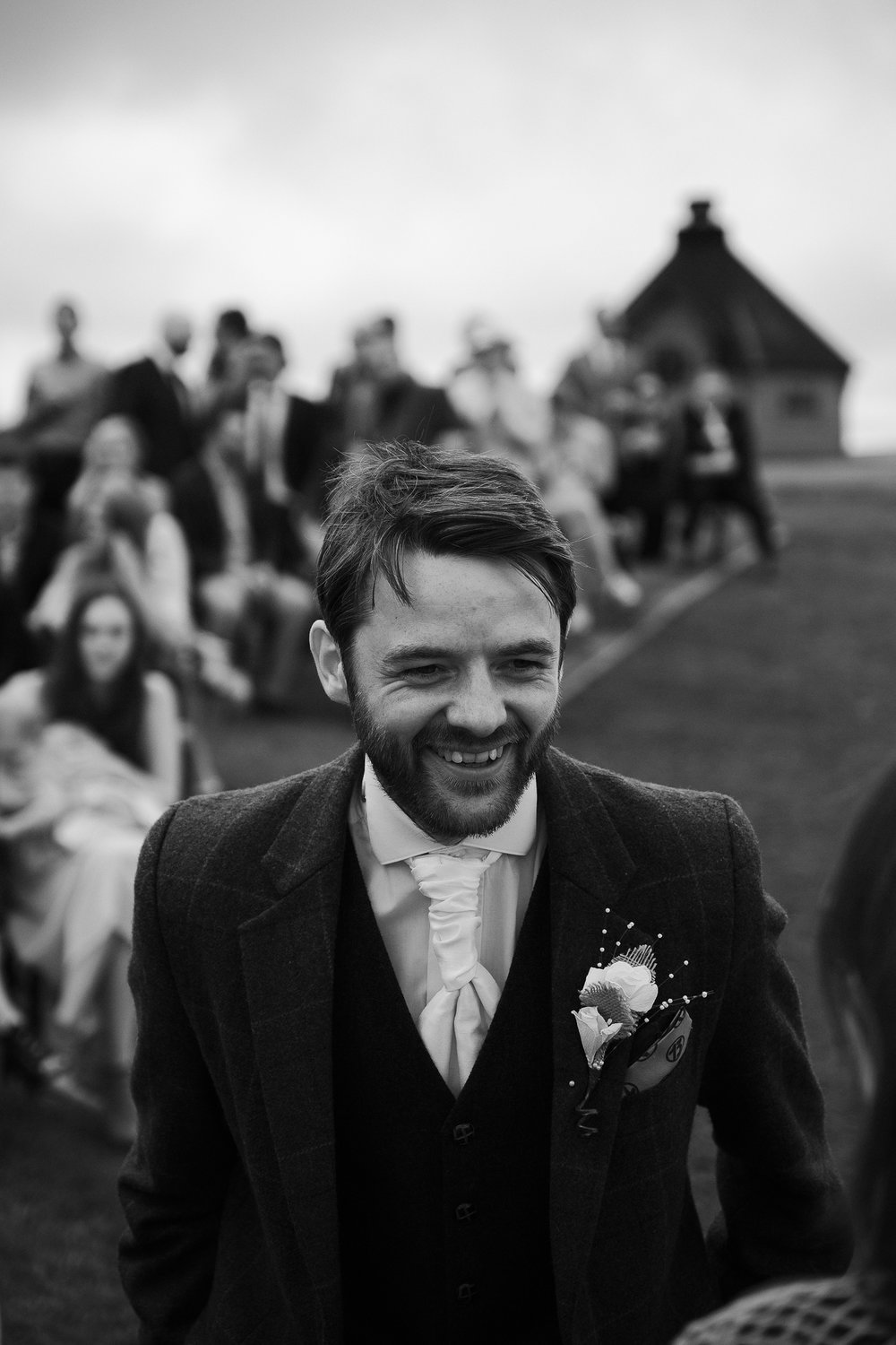 Black and white photo of the groom smiling as he waits for the bride's arrival