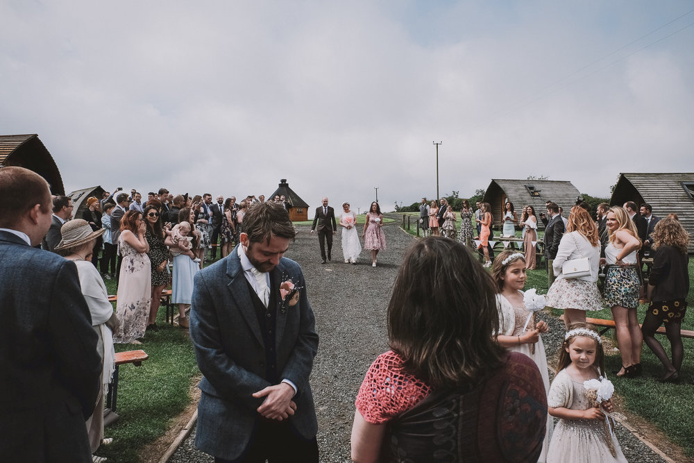 Groom waits nervously as his bride walks down the aisle at an outdoor ceremony