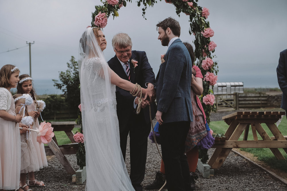 Bride and groom undergo hand fasting ceremony during their outdoor wedding