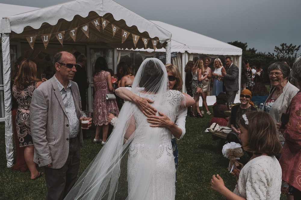 The bride being hugged by a guest outside of the wedding marquee