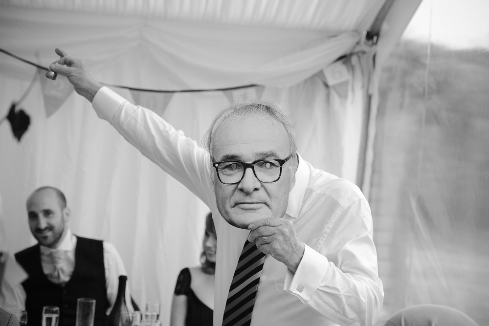 Black and white photo of father of the bride giving speech with Claudio Ranieri mask and bell