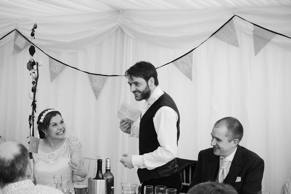Black and white photo of bride pulling a funny face during groom's speech
