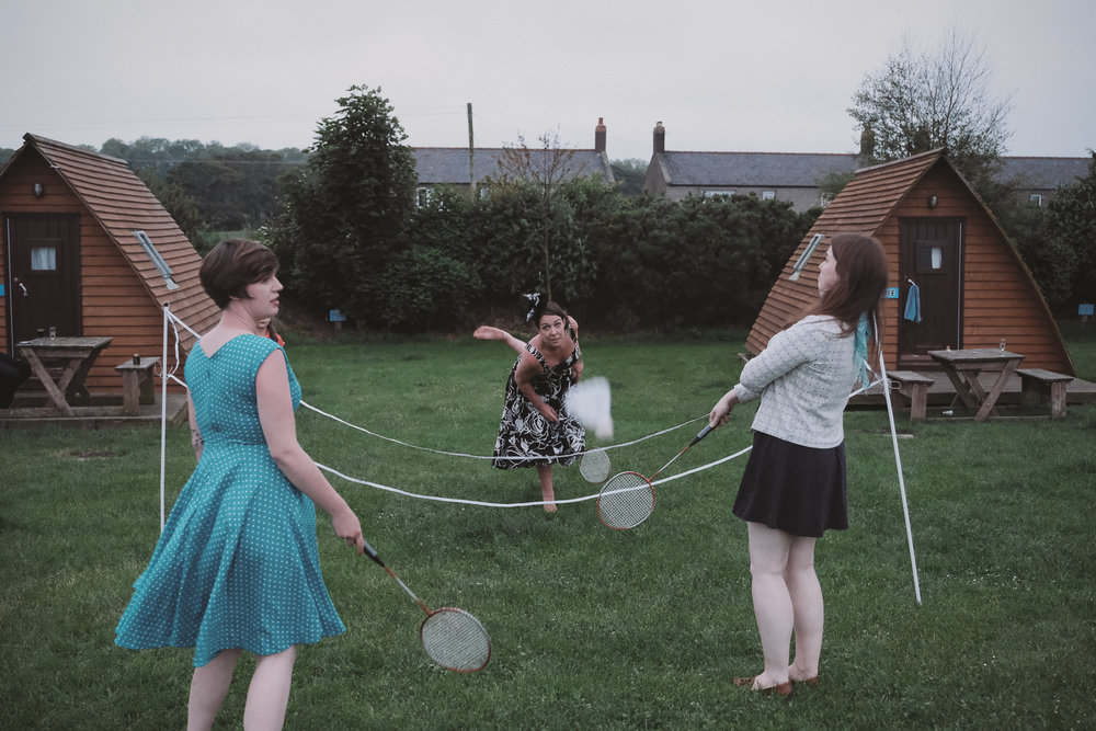 Wedding guests play badminton at an outdoor wedding in Northumberland