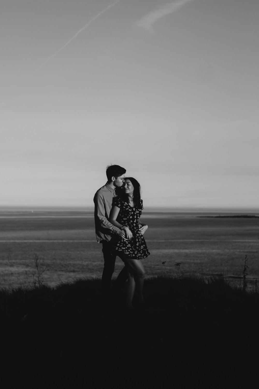 Couple cuddle on clifftop in sexy black and white photo