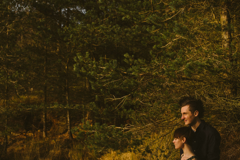 Couple cuddle in the corner of a photo dominated by tree branches deep in the woods