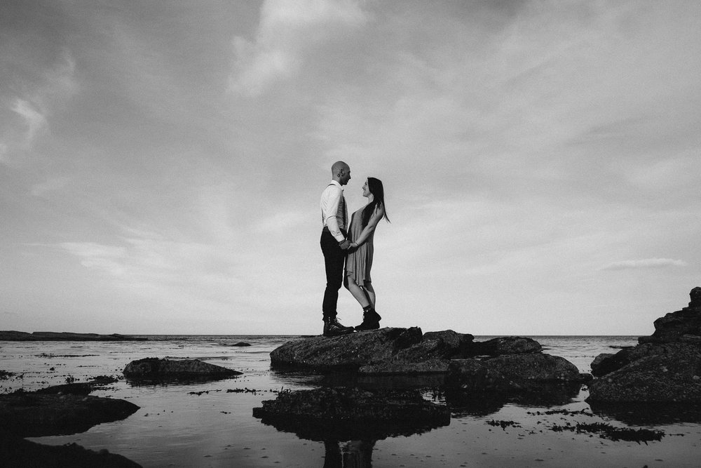 Black and white photo of a couple standing on a rock on the Northumberland coast