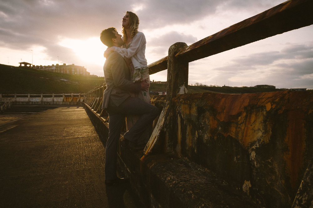 Couple embrace in ruined outdoor swimming pool in warm golden hour light
