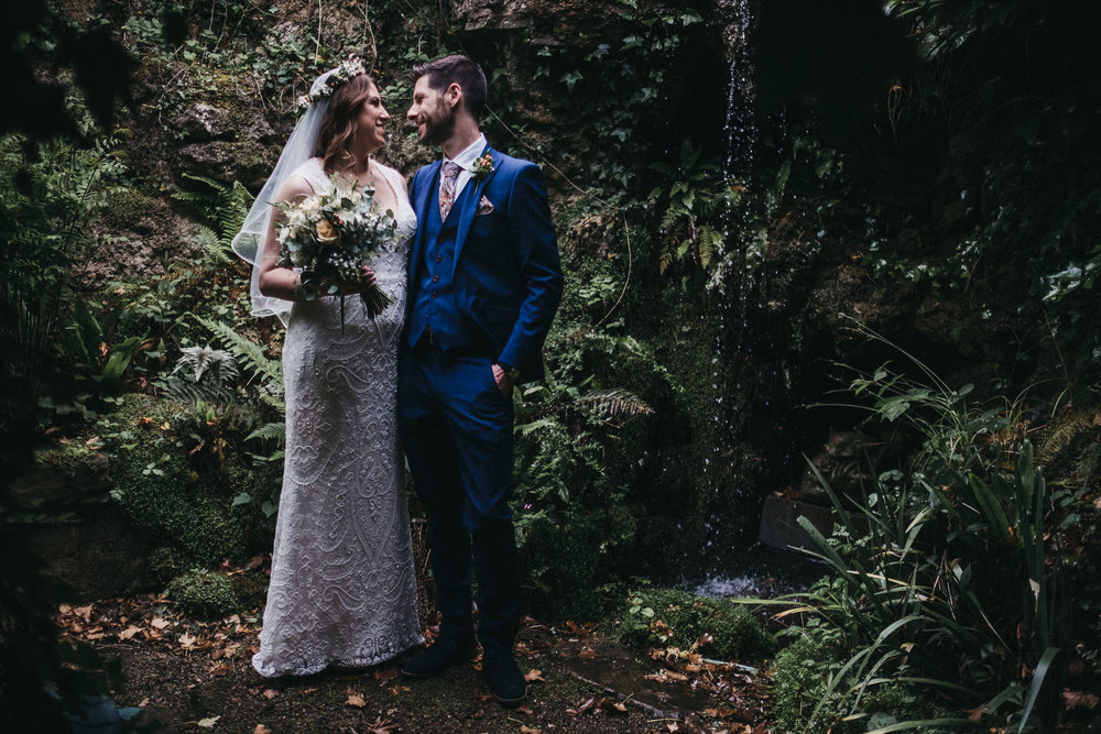 Bride and groom standing in front of small waterfall overgrown with vegetation
