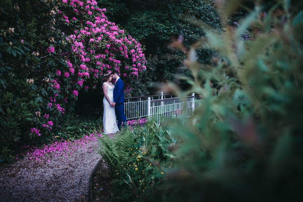 Bride and groom hold hands against a backdrop of pink flowers at Judges at Kirklevington