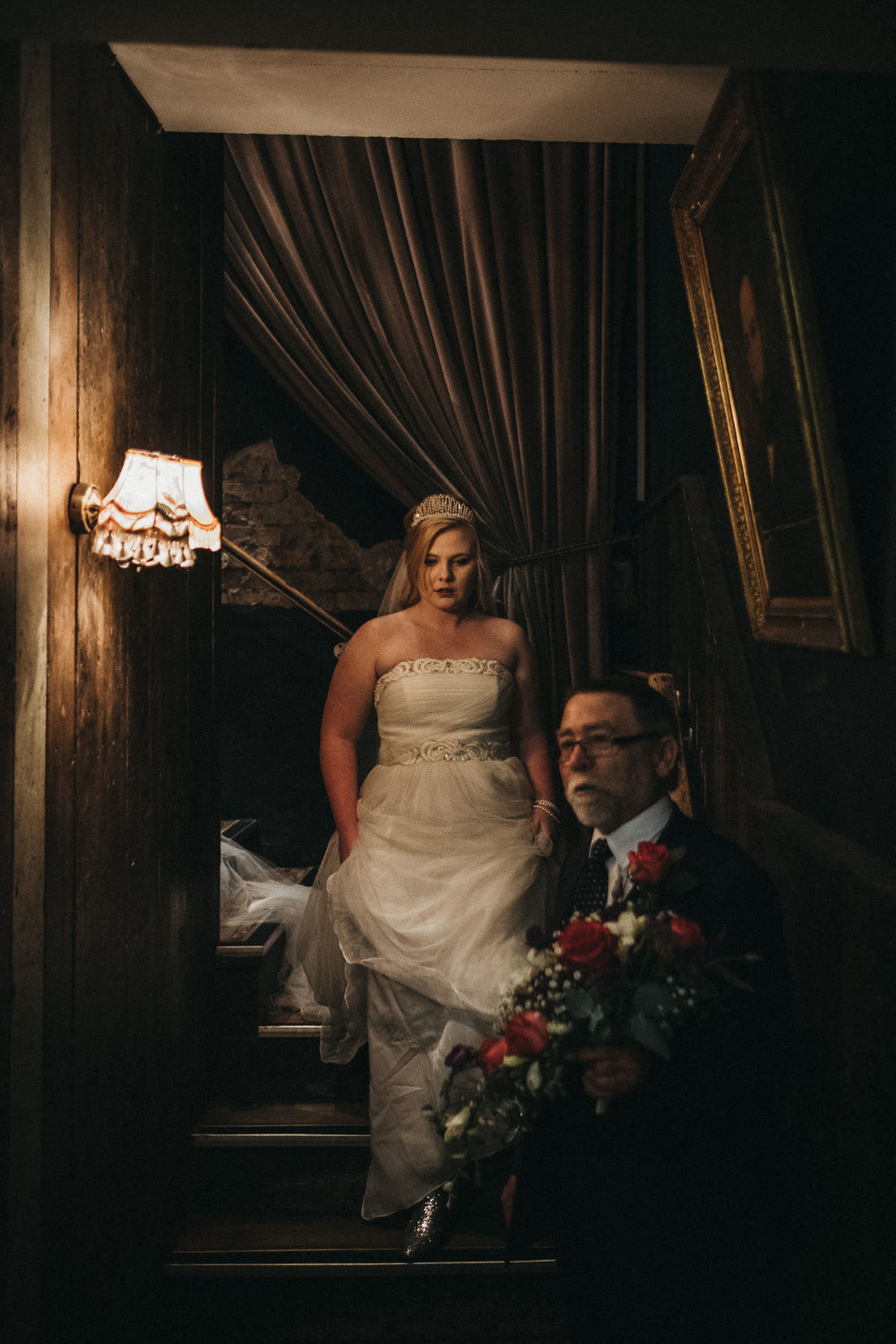 Bride walking down stairs to ceremony in dramatic light at As You Like It Newcastle