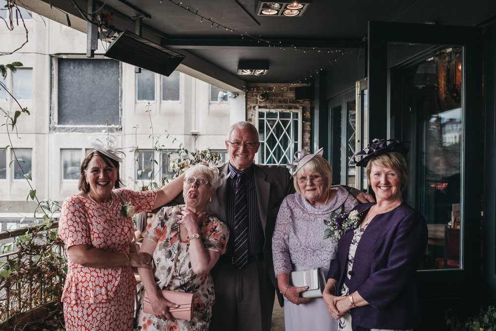 Wedding guest pulls a funny face during a group shot at As You Like It Newcastle upon Tyne