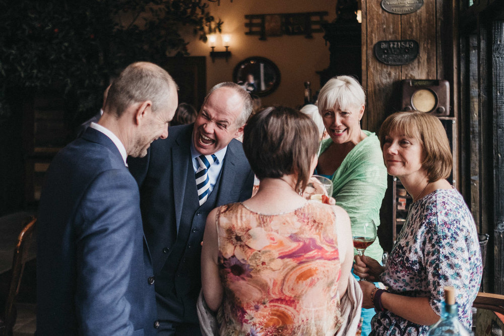 Wedding guest roars with laughter while chatting with other guests at the Old Barn South Causey Inn