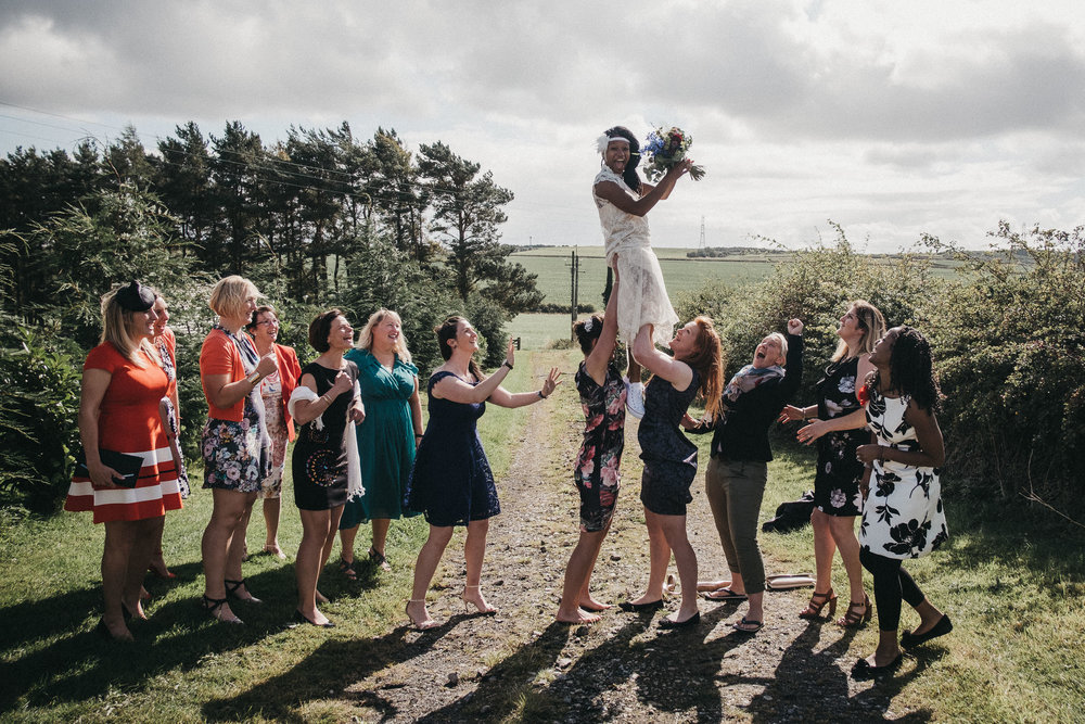 Bride catches flowers as she is held up in rugby line out