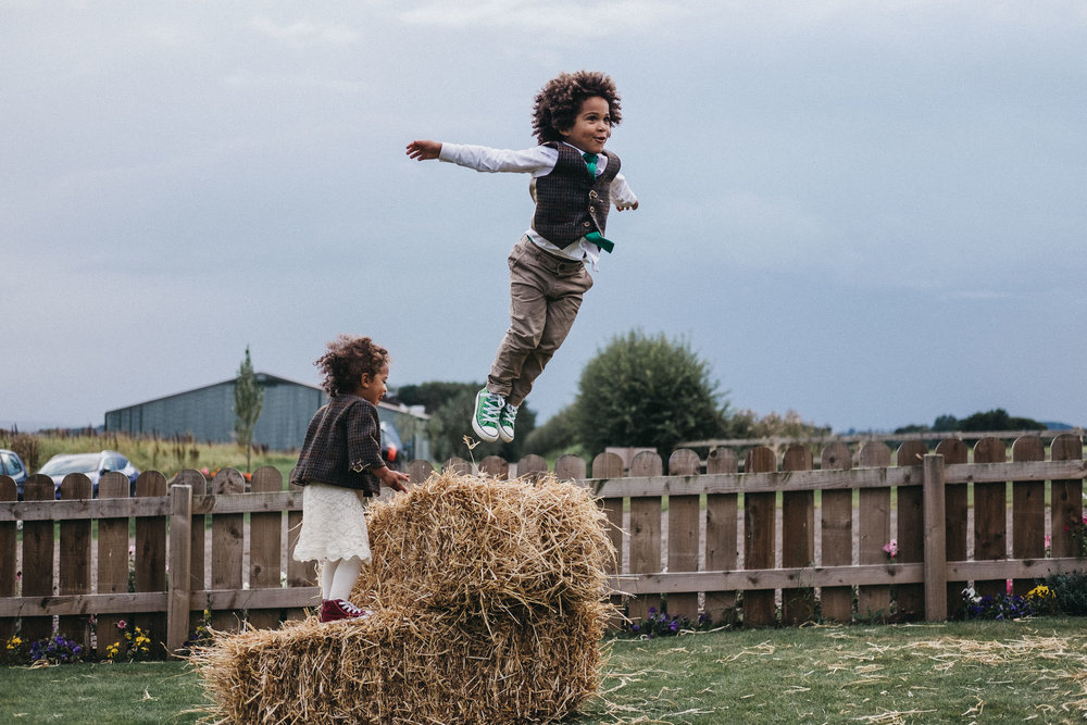 Young boy at wedding jumps from a hay bale