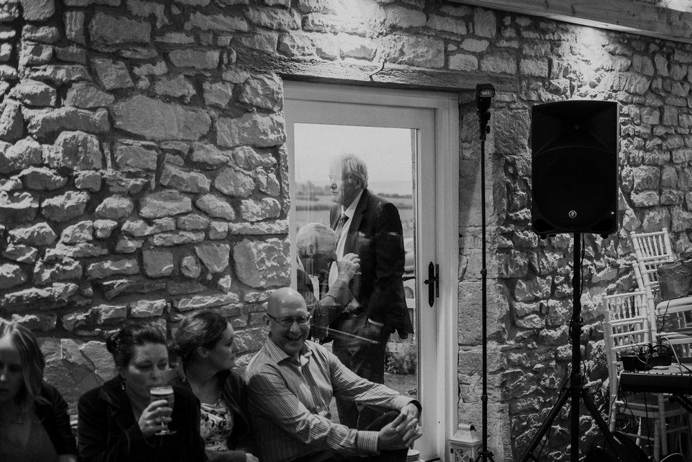 Black and white photo of wedding guest making funny face through a window at Northside Farm
