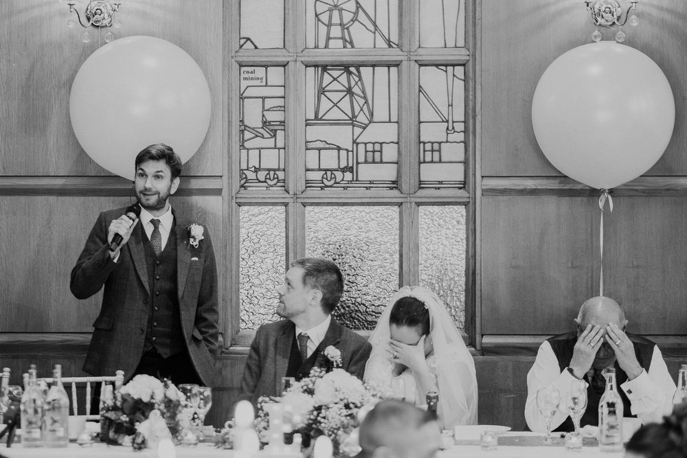black and white photo of the bride and brides father holding their head in their hands during the best man's speech