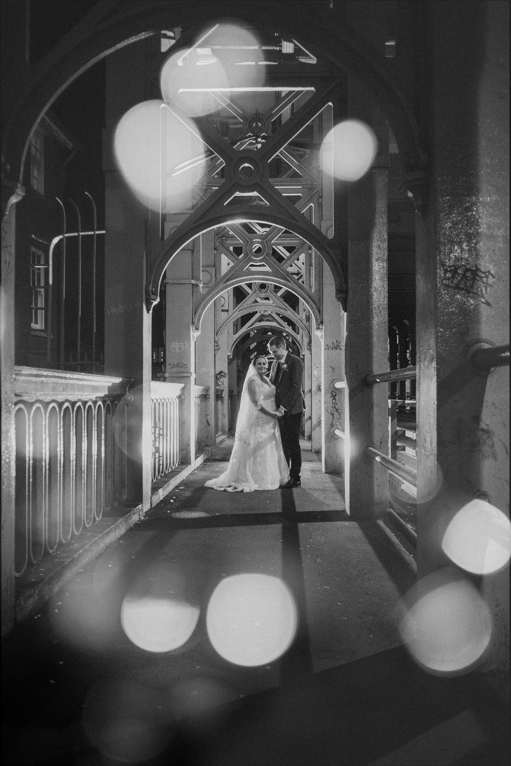 Black and white photo of bride and groom on high level bridge surrounded by fairy lights