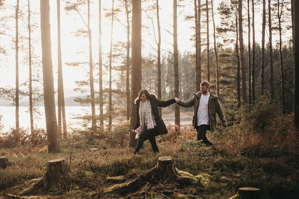 Couple hold hands while picking their way through undergrowth in Kielder Forest