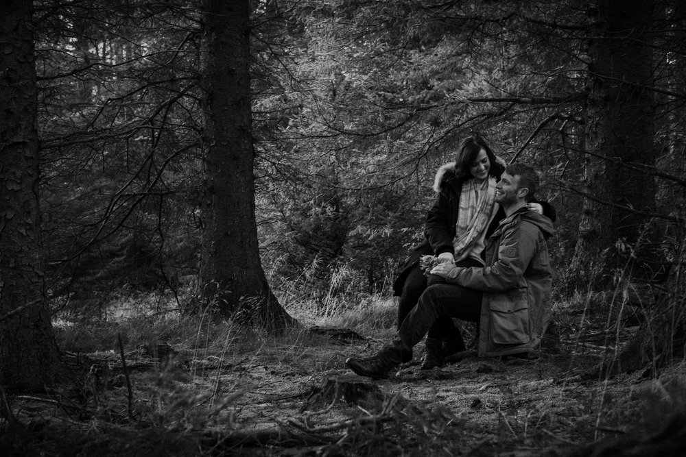 Black and white photo of a couple laughing while sitting on a tree stump in Kielder Forest