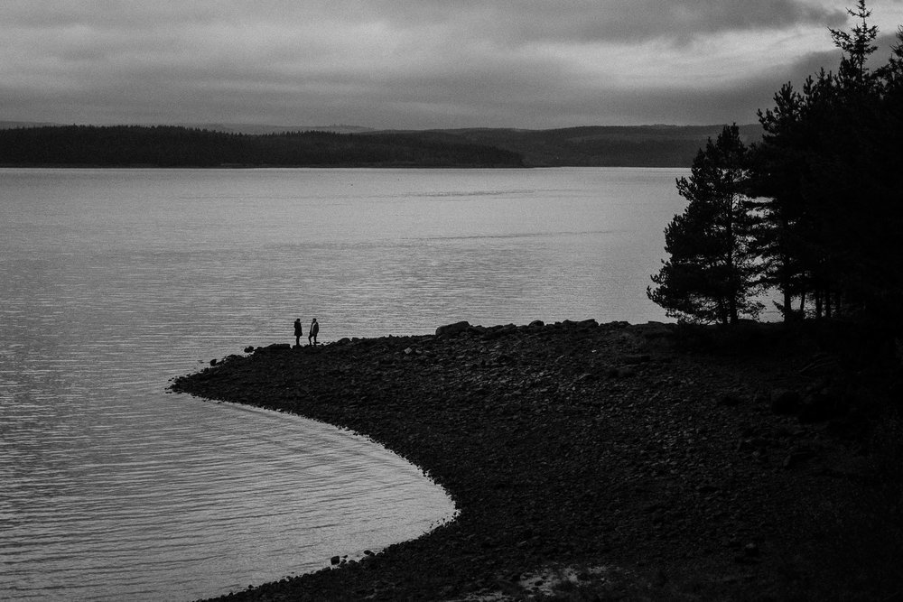 Black and white photo of a couple standing on a spit of land with Kielder Water behind them