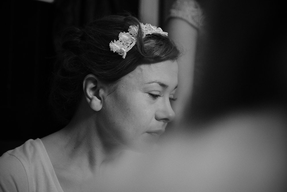 Black and white photo of bride crying during bridal preparations