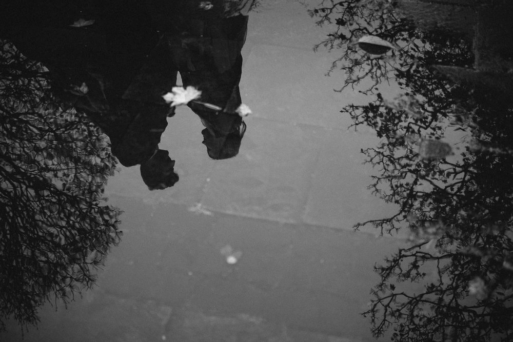 Black and white photo of couple embracing in puddle reflection