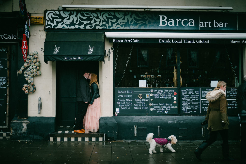 Couple kiss in cafe doorway while woman with dogs walks past