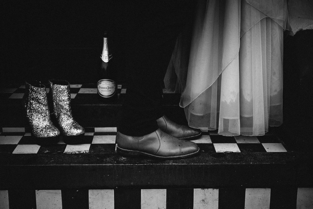 Black and white detail shot of couple's shoes, champagne bottle and glittery boots on tiled step