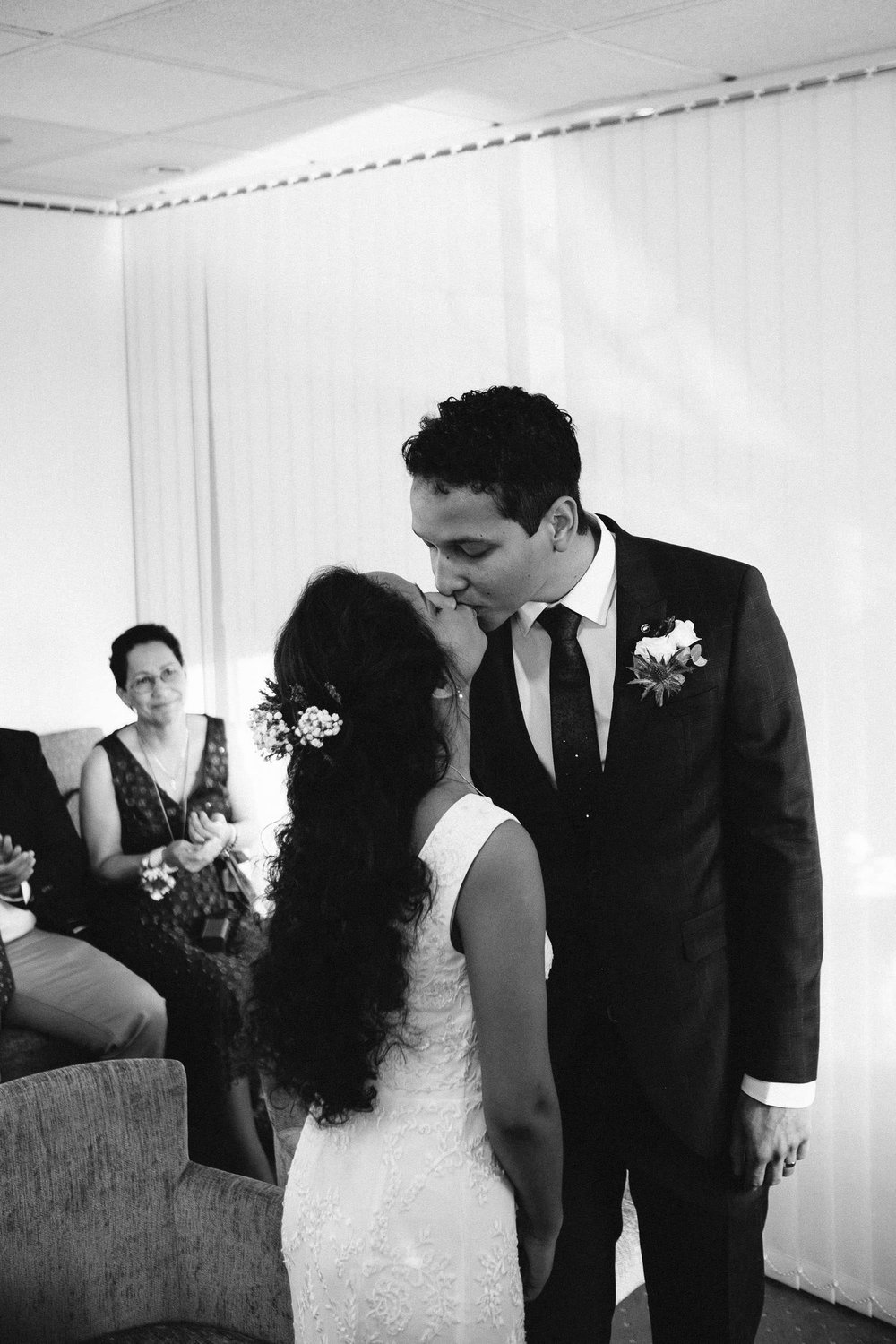 Black and white photo of bride and groom kissing during wedding ceremony