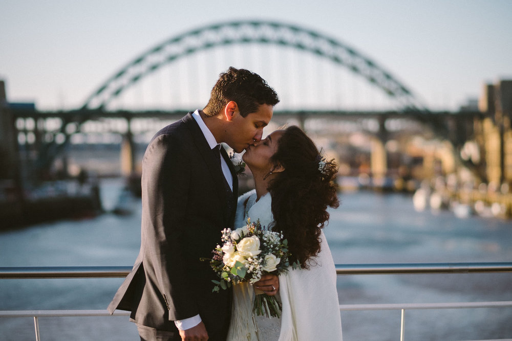 Bride and groom kiss with Tyne Bridge in background