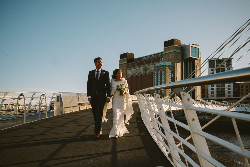 Bride and groom walk over Millennium Bridge with Baltic Art Gallery in the background