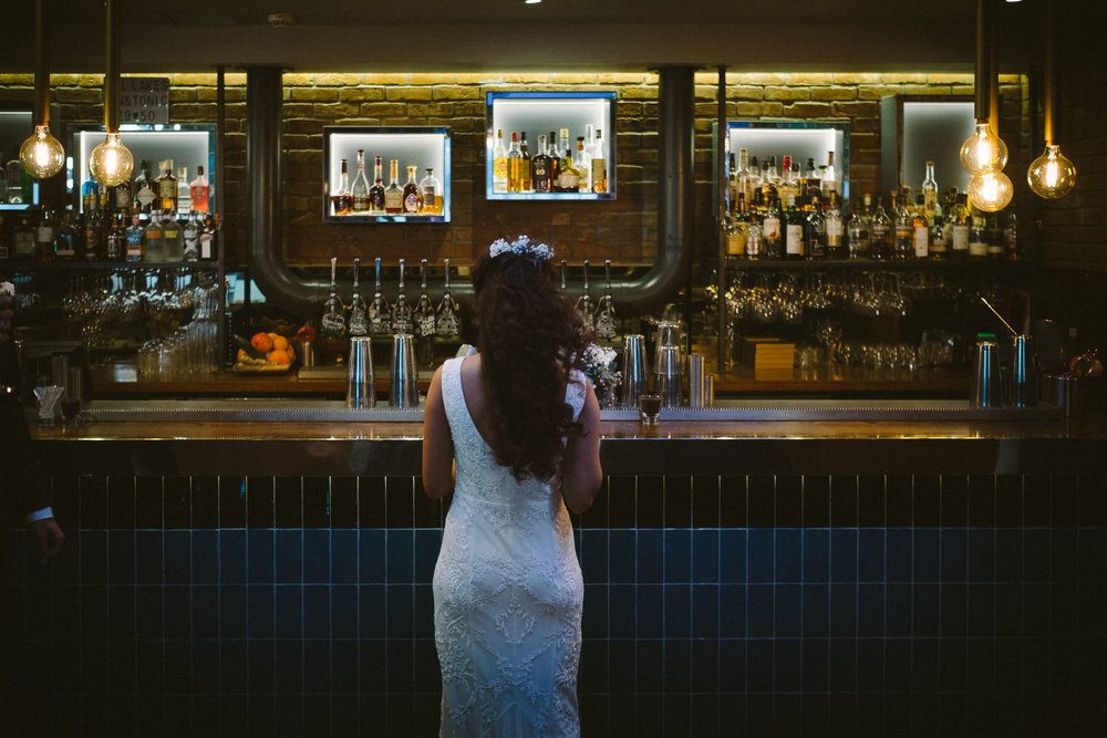 Bride stands in front of colourful bar at Malmaison