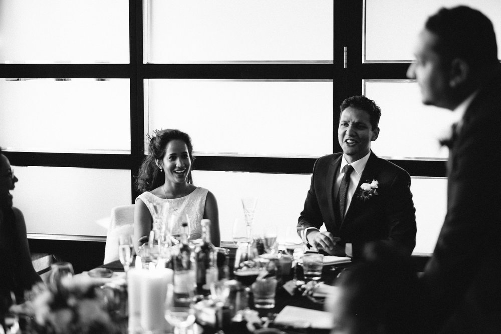 Candid black and white photo of bride and groom laughing at best man's speech