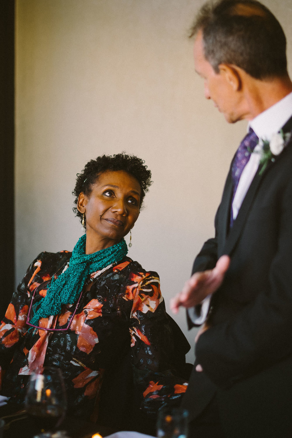 Mother of the groom looks tenderly at father of the bride during his wedding speech