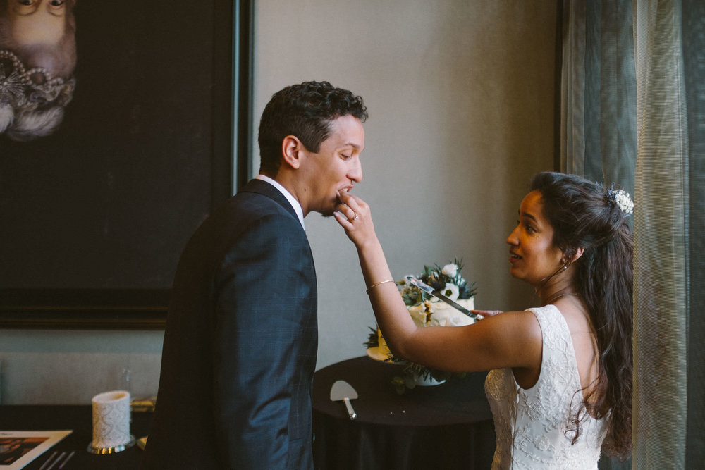 Bride feeds groom some wedding cake