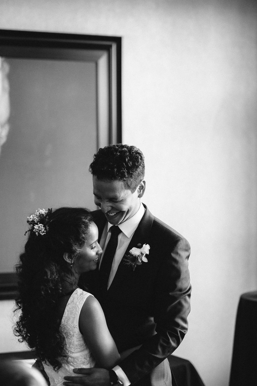 Black and white photo of the bride and groom laughing during first dance