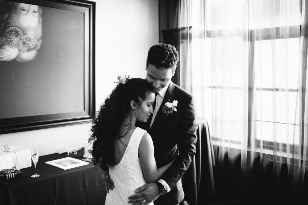 Black and white photo of the bride and groom holding each other during the first dance