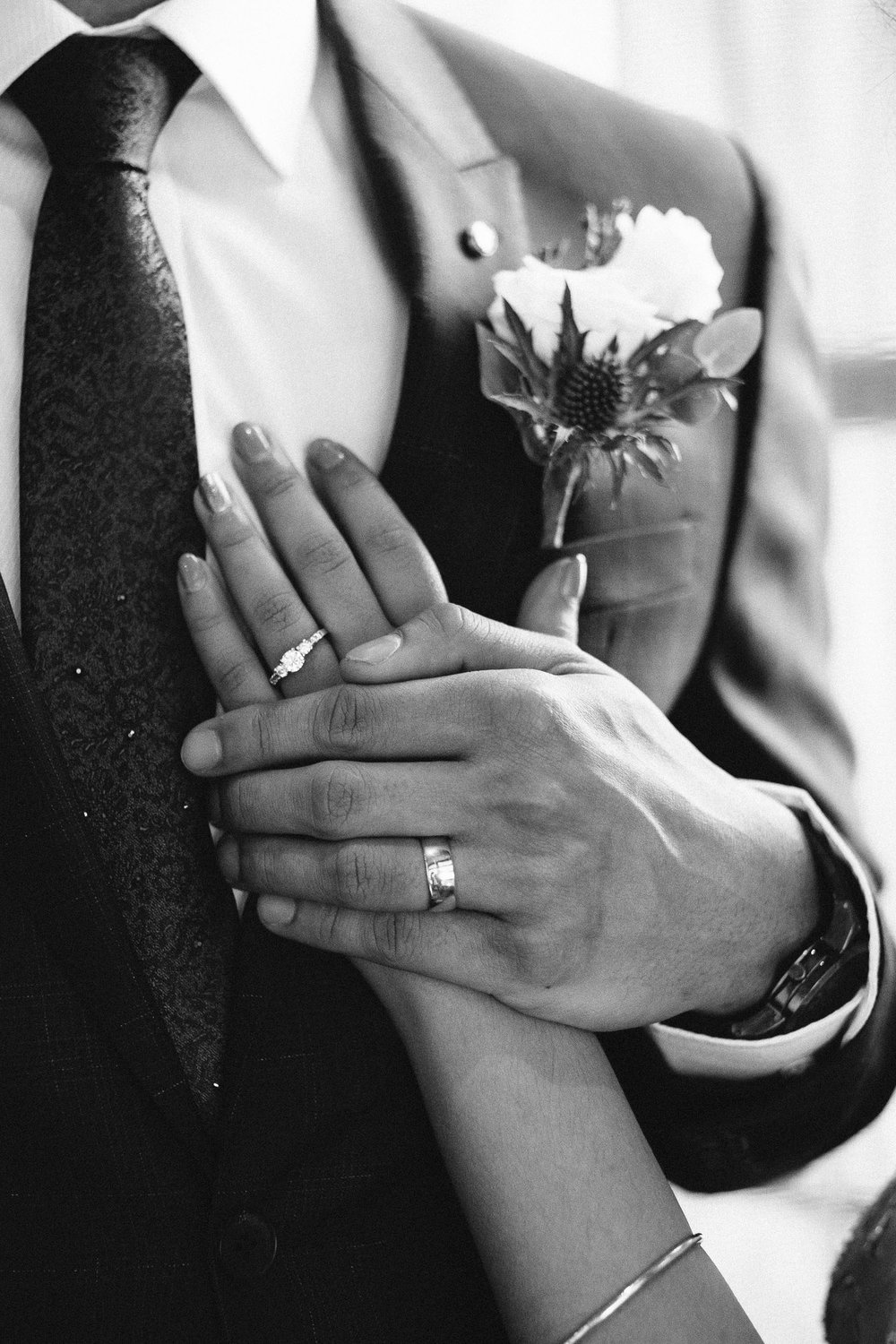 Bride and groom holding hands showing wedding rings in black and white photo