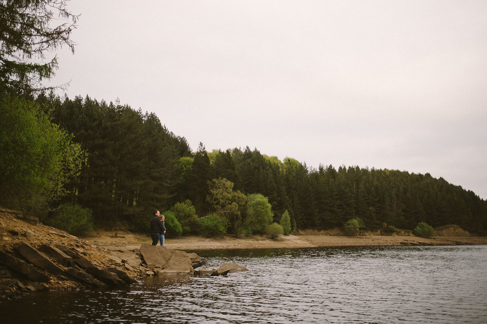 Couple cuddle on a rocky outcrop on reservoir with trees behind