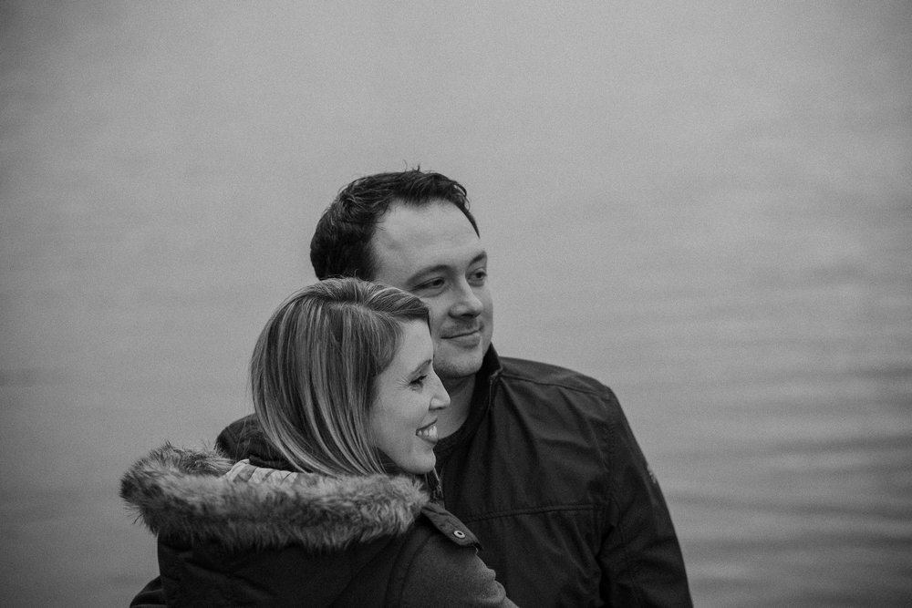 Black and white photo of couple embracing with dogleg reservoir behind