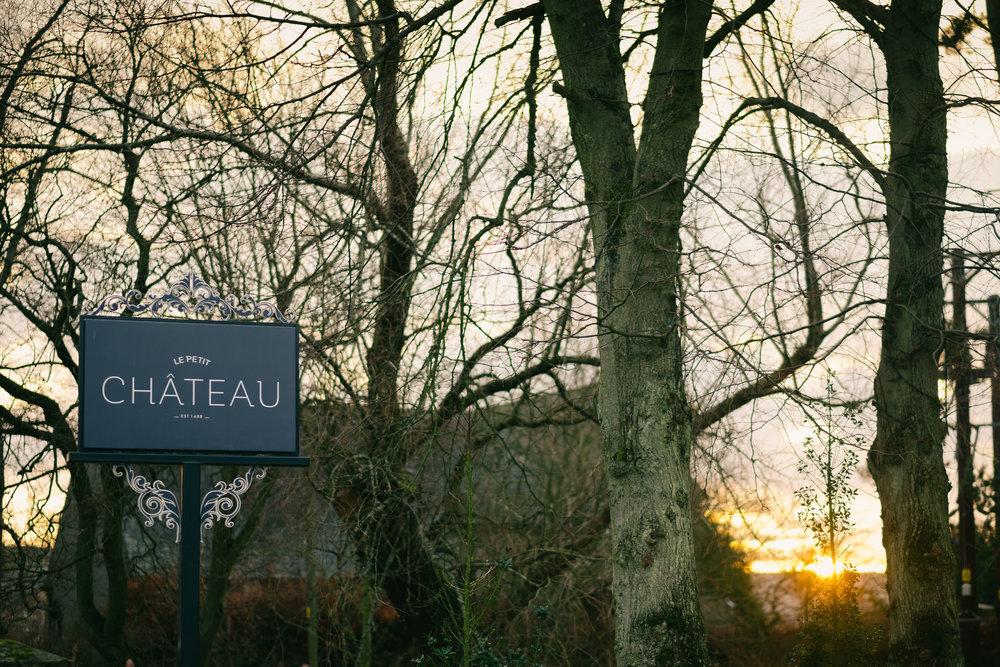 Sign for Le Petit Château as the sun rises