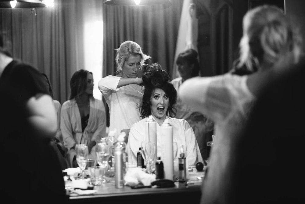 Black and white photo of the bride screaming while getting ready