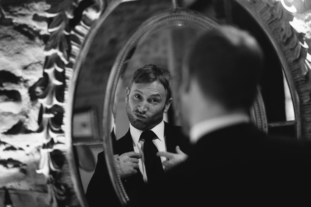 black and white photo of the groom pulling a funny face in the mirror