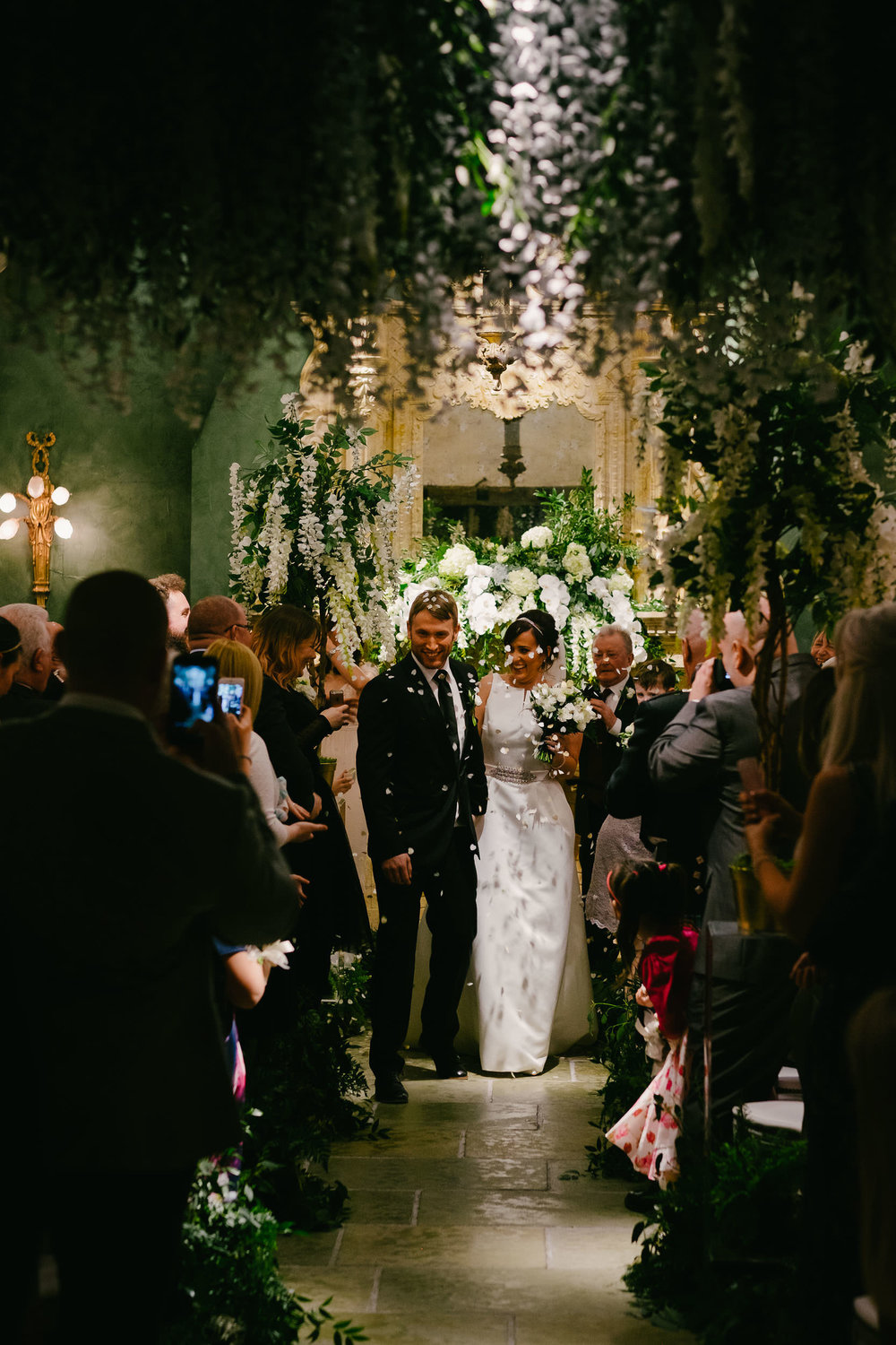 Bride and groom leave ceremony under canopy of flowers