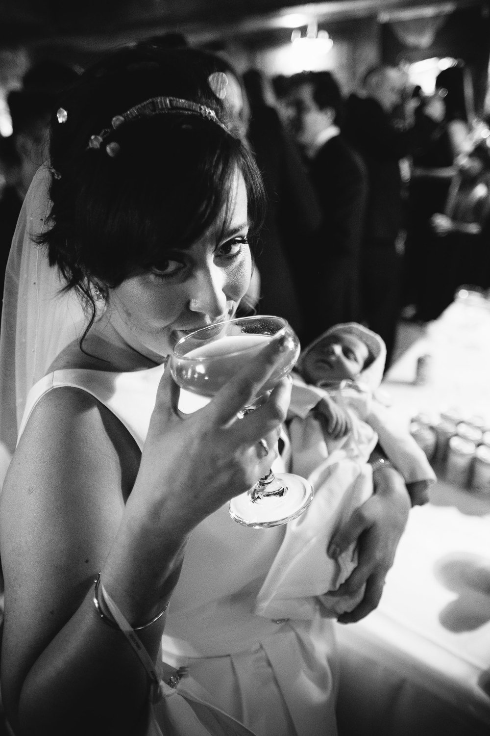 Black and white photo of bride sipping cocktail while holding baby