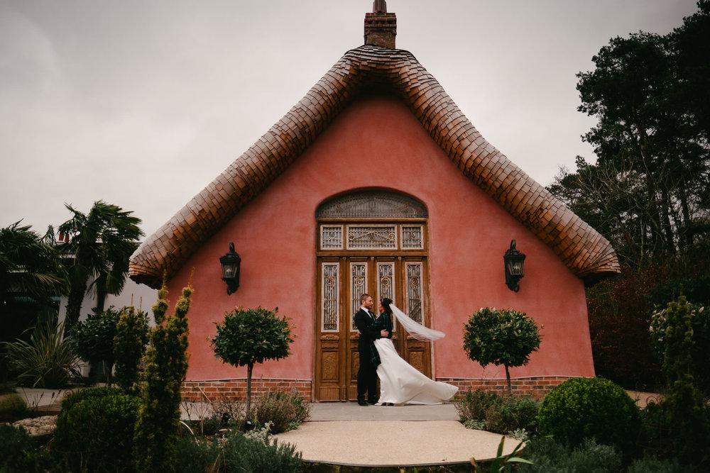 Bride and groom pose outside Le Petit Château